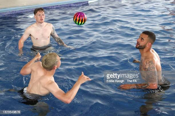 Phil Foden, Jordan Pickford and Kyle Walker of England head a ball to each other in a swimming pool during a recovery session at St George's Park on...