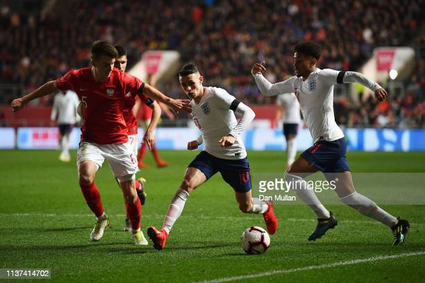 Phil Foden of England gets past the tackle from Karol Fila of Poland during the U21 International Friendly match between England and Poland at Ashton...