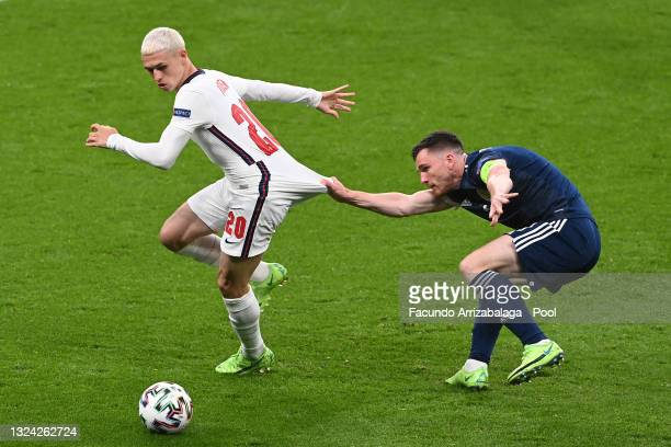 Phil Foden of England is pulled back by Andrew Robertson of Scotland during the UEFA Euro 2020 Championship Group D match between England and...