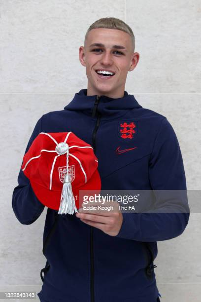 Phil Foden of England poses with an England legacy cap at St George's Park on June 08, 2021 in Burton upon Trent, England.