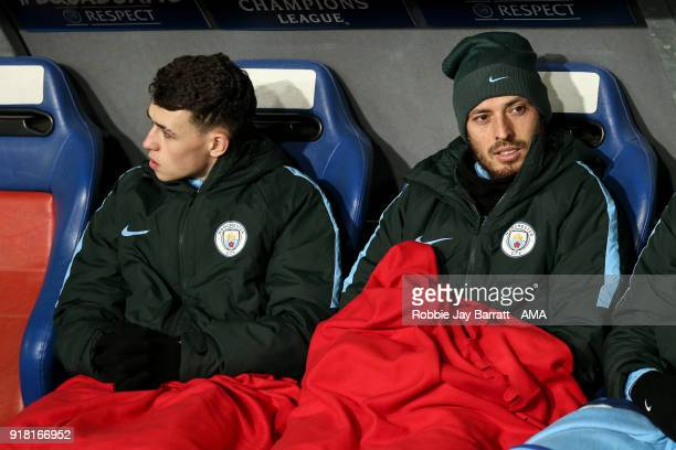 Phil Foden of Manchester City and David Silva of Manchester City sit on the bench under blankets during the UEFA Champions League Round of 16 First...