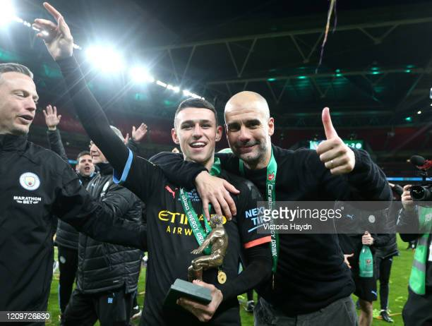 Phil Foden of Manchester City and Pep Guardiola, Manager of Manchester City pose with the trophy following their sides victory during the Carabao Cup...