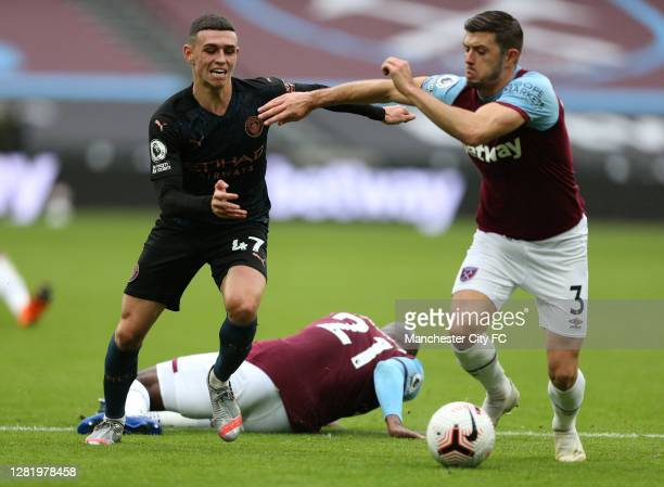 Phil Foden of Manchester City battles for possession with Aaron Cresswell of West Ham United and Angelo Ogbonna of West Ham United lays on the pitch...