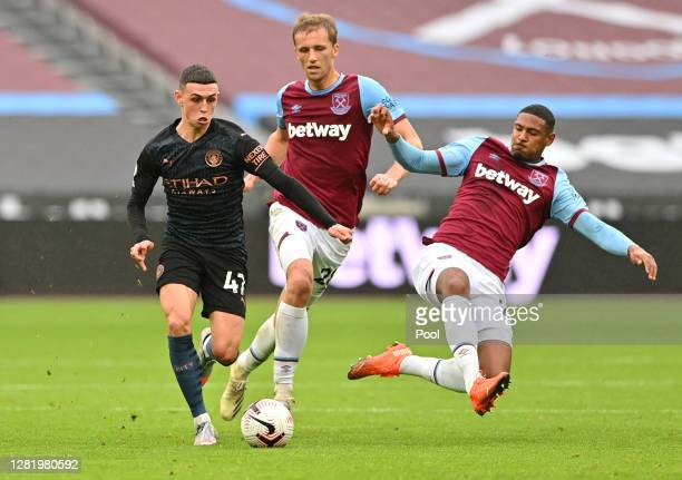 Phil Foden of Manchester City battles for possession with Tomas Soucek of West Ham United during the Premier League match between West Ham United and...
