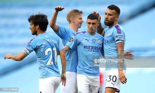 Phil Foden of Manchester City celebrate with his team after scoring his teams first goal during the Premier League match between Manchester City and...