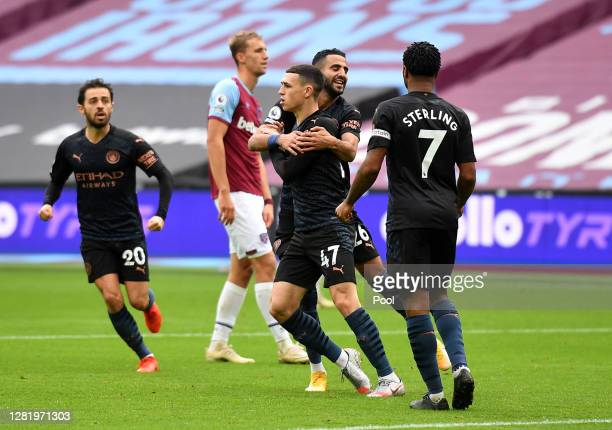 Phil Foden of Manchester City celebrates after scoring his team's first goal with Riyad Mahrez of Manchester City and Raheem Sterling of Manchester...