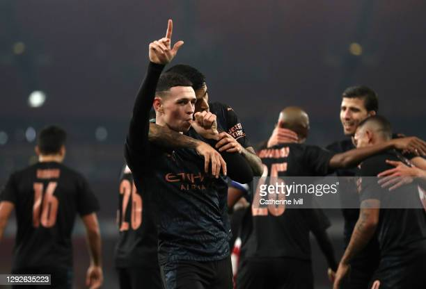 Phil Foden of Manchester City celebrates after scoring their sides third goal with teammate Joao Cancelo during the Carabao Cup Quarter Final match...