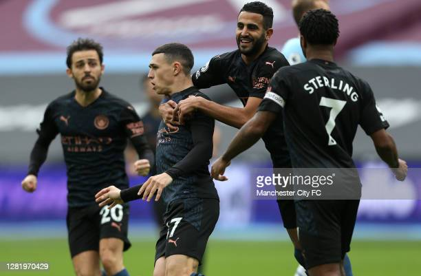 Phil Foden of Manchester City celebrates with his team after scoring his sides first goal during the Premier League match between West Ham United and...