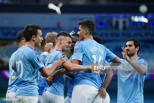 Phil Foden of Manchester City celebrates with his team mates after scoring his team's third goal during the Premier League match between Manchester...