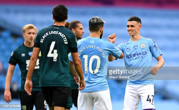 Phil Foden of Manchester City celebrates with Sergio Aguero of Manchester City after scoring his teams first goal during the Premier League match...