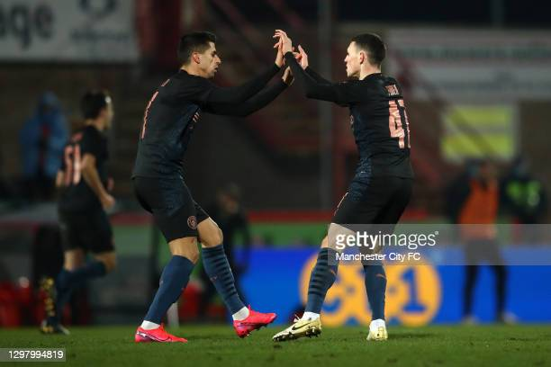 Phil Foden of Manchester City celebrates with team mate Joao Cancelo after scoring their sides first goal during The Emirates FA Cup Fourth Round...
