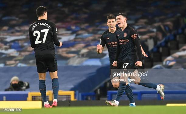 Phil Foden of Manchester City celebrates with team mates Joao Cancelo and Ruben Dias after scoring their side's first goal during the Premier League...