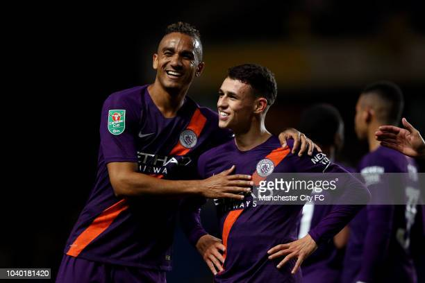 Phil Foden of Manchester City celebrates with teammate Danilo after scoring his team's third goal during the Carabao Cup Third Round match between...
