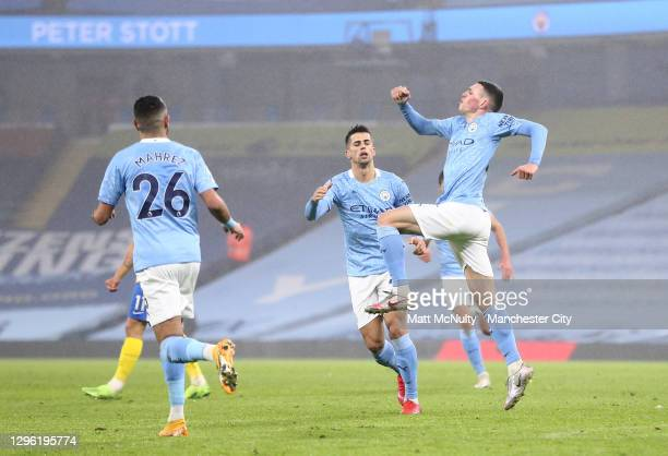 Phil Foden of Manchester City celebrates with teammate Joao Cancelo after scoring their team's first goal during the Premier League match between...