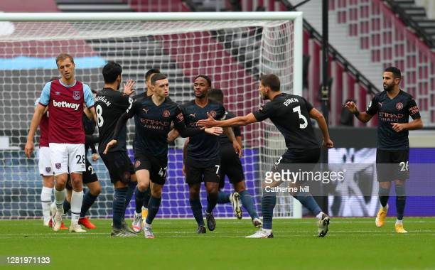 Phil Foden of Manchester City celebrates with teammates after scoring his sides first goal during the Premier League match between West Ham United...