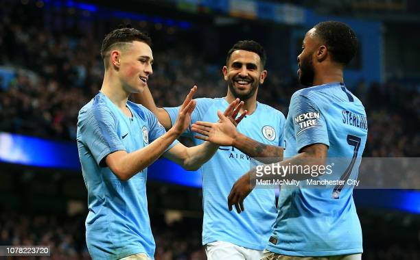 Phil Foden of Manchester City celebrates with teammates Raheem Sterling and Riyad Mahrez after scoring his team's second goal during the FA Cup Third...