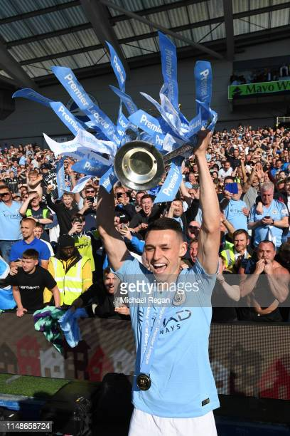 Phil Foden of Manchester City celebrates with the Premier League Trophy after winning the title following the Premier League match between Brighton &...