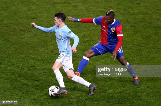 Phil Foden of Manchester City competes with Serey Die of Basel during the UEFA Champions League Round of 16 Second Leg match between Manchester City...