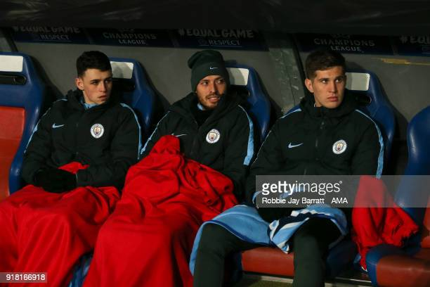 Phil Foden of Manchester City David Silva of Manchester City and John Stones of Manchester City sit on the bench under blankets during the UEFA...