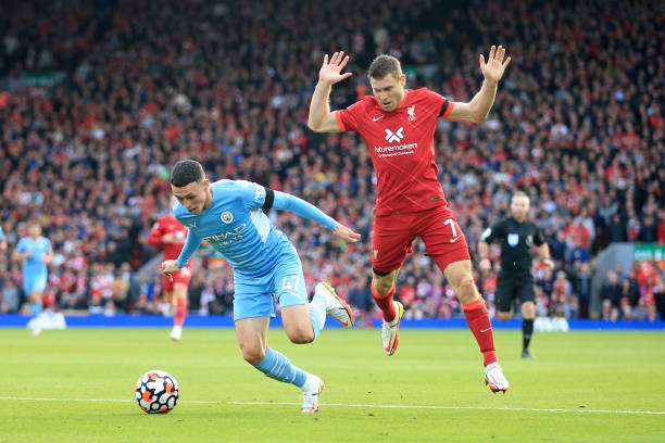Phil Foden of Manchester City goes down under a challenge from James Milner of Liverpool but no penalty was awarded during the Premier League match...