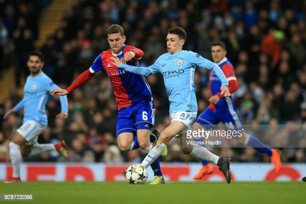 Phil Foden of Manchester City holds off pressure from Fabian Frei of FC Basel during the UEFA Champions League Round of 16 Second Leg match between...
