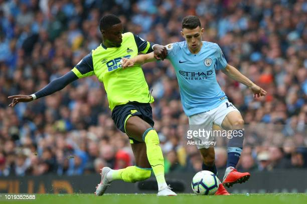 Phil Foden of Manchester City is challenged by Adama Diakhaby of Huddersfield Town during the Premier League match between Manchester City and...