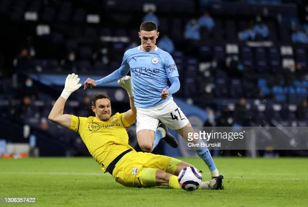 Phil Foden of Manchester City is challenged by Alex McCarthy of Southampton during the Premier League match between Manchester City and Southampton...