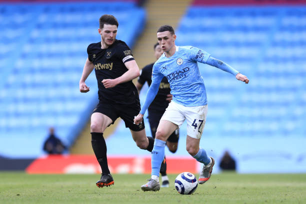 Phil Foden of Manchester City is challenged by Declan Rice of West Ham United during the Premier League match between Manchester City and West Ham...