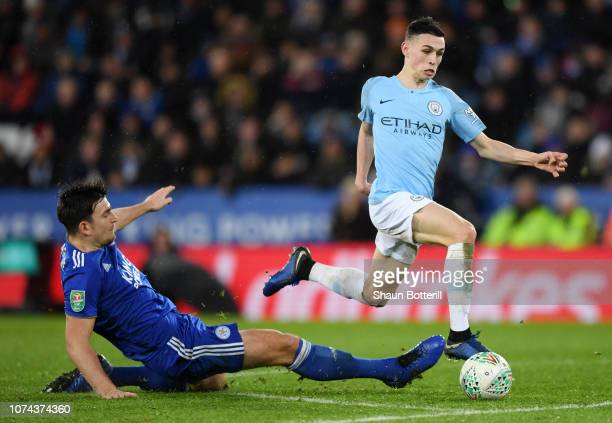 Phil Foden of Manchester City is challenged by Harry Maguire of Leicester City during the Carabao Cup Quarter Final match between Leicester City and...