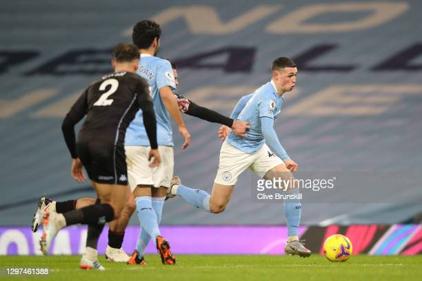 Phil Foden of Manchester City is challenged by Jack Grealish of Aston Villa during the Premier League match between Manchester City and Aston Villa...