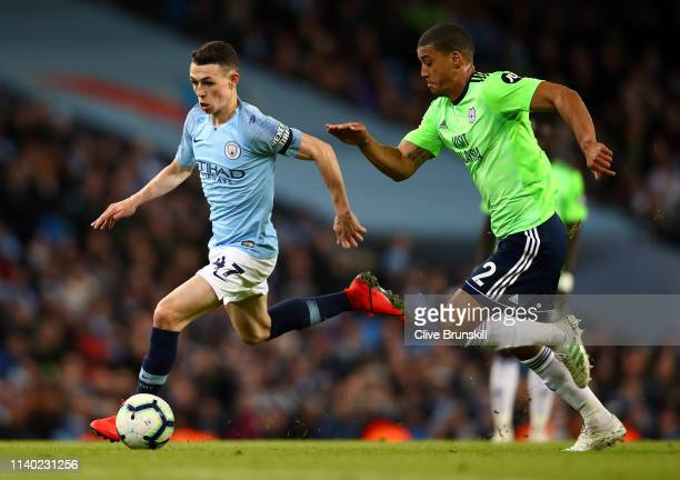 Phil Foden of Manchester City is challenged by Lee Peltier of Cardiff City during the Premier League match between Manchester City and Cardiff City...