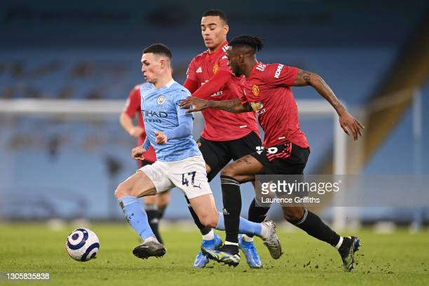 Phil Foden of Manchester City is challenged by Mason Greenwood and Aaron Wan-Bissaka of Manchester United during the Premier League match between...