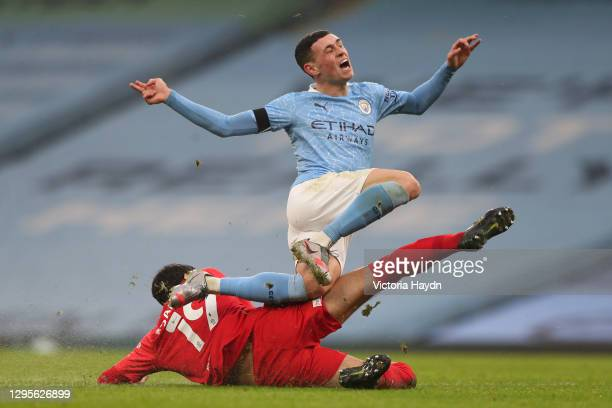 Phil Foden of Manchester City is tackled by Mikel San Jose of Birmingham City during the FA Cup Third Round match between Manchester City and...