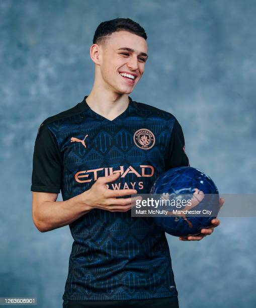 Phil Foden of Manchester City poses wearing the 2020/21 Puma away jersey at the City Football Academy on August 03, 2020 in Manchester, England.