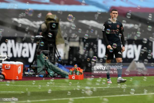 Phil Foden of Manchester City prepares to come on as a substitute during the Premier League match between West Ham United and Manchester City at...