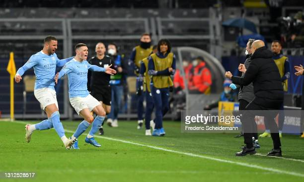 Phil Foden of Manchester City runs towards Pep Guardiola, Manager of Manchester City as he celebrates with team mate Kyle Walker after scoring their...
