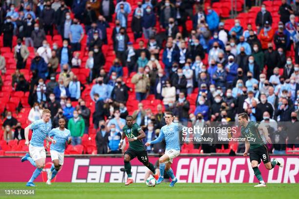 Phil Foden of Manchester City runs with the ball as Manchester City fans watch on from the stand during the Carabao Cup Final between Manchester City...