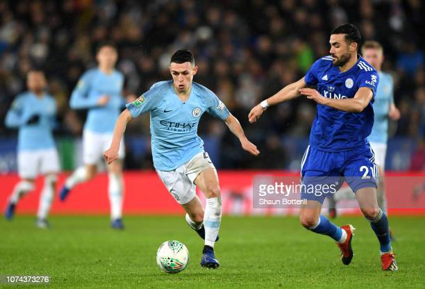 Phil Foden of Manchester City runs with the ball under pressure from Vicente Iborra of Leicester City during the Carabao Cup Quarter Final match...