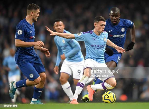 Phil Foden of Manchester City runs with the ball under pressure from Kurt Zouma and Mateo Kovacic of Chelsea during the Premier League match between...