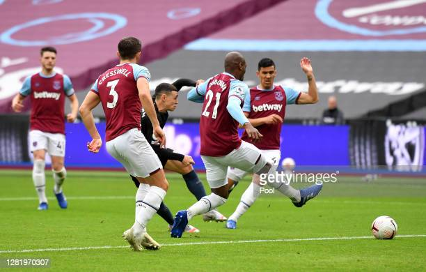 Phil Foden of Manchester City scores his team's first goal during the Premier League match between West Ham United and Manchester City at London...