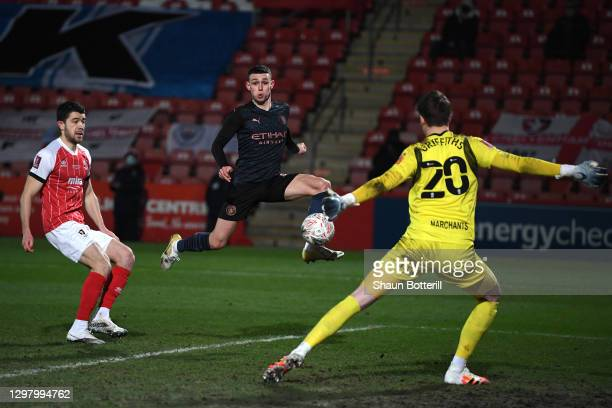 Phil Foden of Manchester City scores their sides first goal past Josh Griffiths of Cheltenham Town during The Emirates FA Cup Fourth Round match...