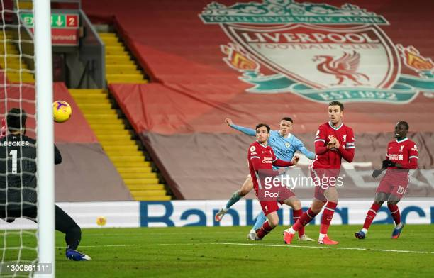 Phil Foden of Manchester City scores their side's fourth goal past Alisson Becker of Liverpool whilst under pressure from Andy Robertson of Liverpool...