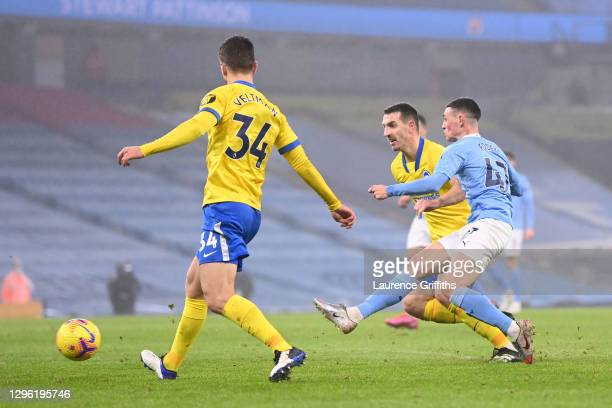 Phil Foden of Manchester City scores their team's first goal under pressure from Lewis Dunk of Brighton and Hove Albion during the Premier League...