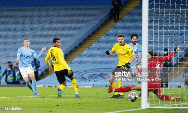 Phil Foden of Manchester City scores their team's second goal past Manuel Akanji of Borussia Dortmund during the UEFA Champions League Quarter Final...