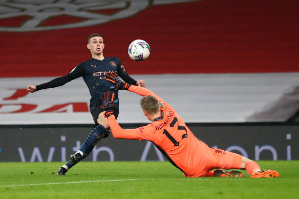 Phil Foden of Manchester City scores their team's third goal during the Carabao Cup Quarter Final match between Arsenal and Manchester City at...