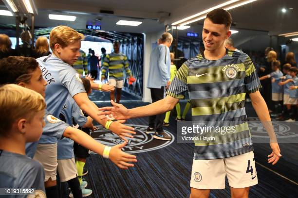 Phil Foden of Manchester City shakes hands with fans in the tunnel prior to the Premier League match between Manchester City and Huddersfield Town at...