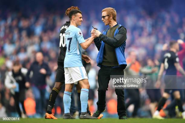 Phil Foden of Manchester City speaks with fans as they invade the pitch following the Premier League match between Manchester City and Swansea City...