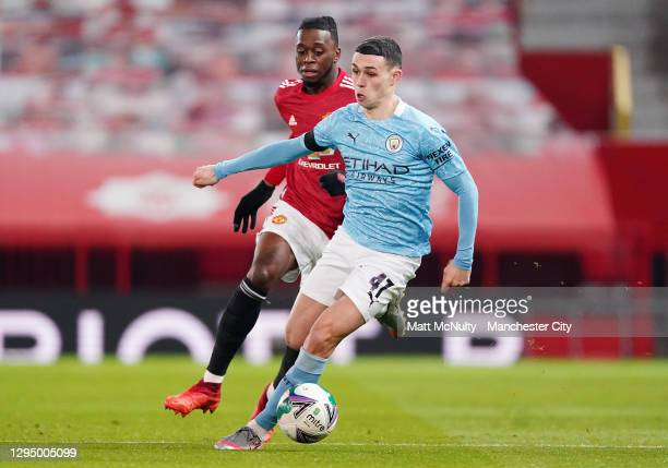 Phil Foden of Manchester City takes on Aaron Wan Bissaka of Manchester United during the Carabao Cup Semi Final match between Manchester United and...