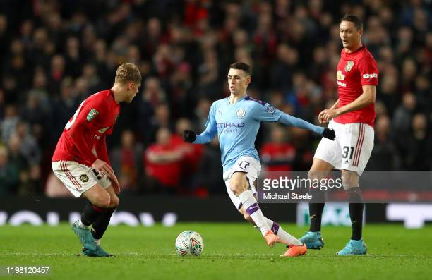 Phil Foden of Manchester City takes the ball past Brandon Williams of Manchester United during the Carabao Cup Semi Final match between Manchester...