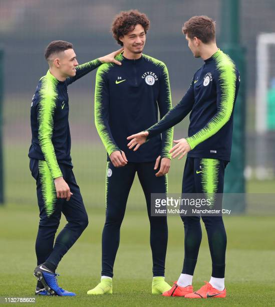 Phil Foden Philippe Sandler and John Stones talk during the training session at Manchester City Football Academy on February 28 2019 in Manchester...